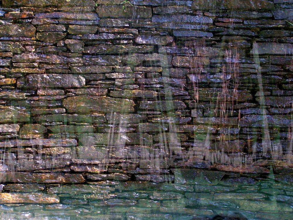 Wasserfall über eine Trockenmauer aus Porphyr