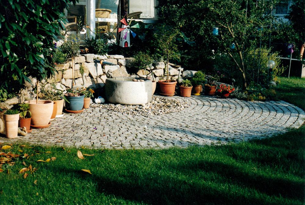 Pflaster: Rondell aus Natursteinpflaster Klienpflaster Granit; Trockenmauer Granit, Sandsteinbrunnen