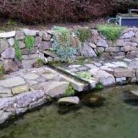 Einfassung einer natürlichen Quelle mit einer Granitrinne in den natürlichen Gartenteich und umlaufende Granit-Findling-Mauer und -Pflaster